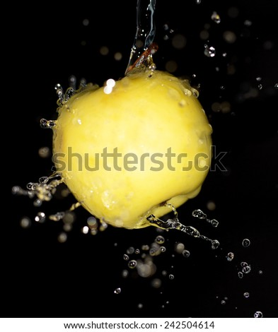 yellow apple in water on a black background - stock photo