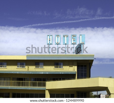 Yellow architecture and turquoise sign on an old hotel. - stock photo