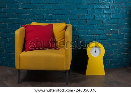 Yellow arm-chair in blue urban loft interior - stock photo