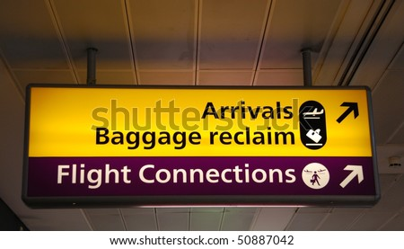 yellow arrivals/baggage claim and puprle flight connections sign at a international airport - stock photo
