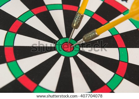 Yellow arrow hitting in the target center  of dartboard - stock photo
