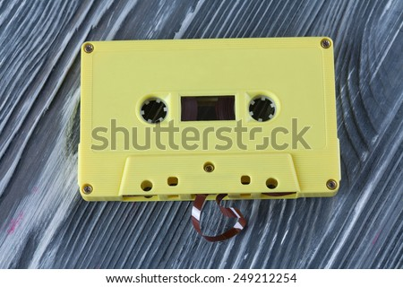 Yellow audio cassette on the gray wooden background. Vintage, retro style. Soft focus. - stock photo