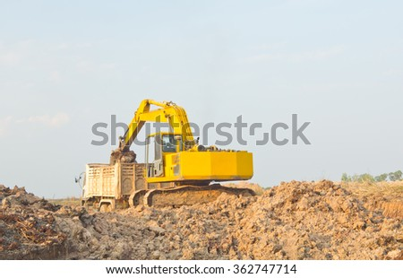 Yellow backhoe working digging for the construction of reservoirs in rural areas.