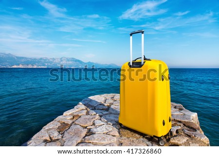 Yellow bag on stone pier. Travel concept  - stock photo
