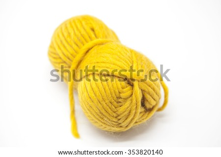 Yellow ball of wool yarn for knitting close up on a white background