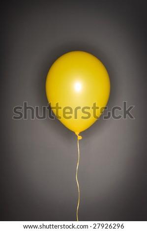 yellow balloon on gray background - stock photo