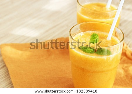 Yellow banana smoothie with mint and green tea decorated with a small brunch of green french mint. Natural napkin background. Vertical. - stock photo