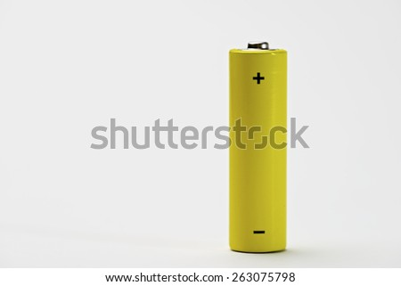 Yellow battery on a white table. - stock photo