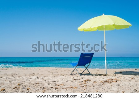 Yellow beach umbrella and lounge chair on a beach in Sardinia