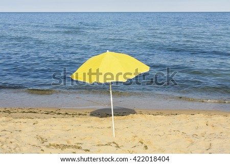 Yellow beach umbrella near sea on sandy beach. - stock photo