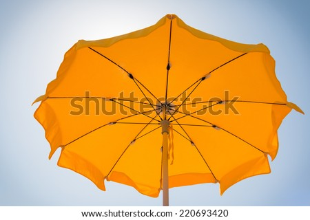 yellow beach umbrella under the sun near the sea; blue sky background. - stock photo