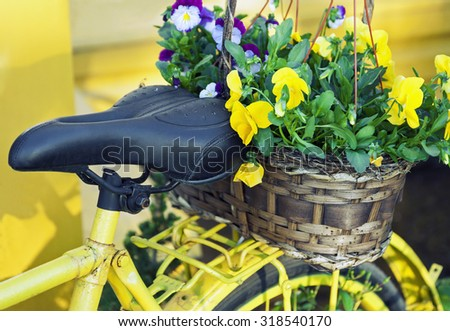 Yellow bicycle decorated with basket full of flowers - stock photo