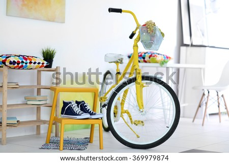 Yellow bicycle with sneakers in light living room interior - stock photo