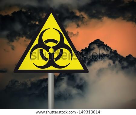 Yellow biohazard warning sign on against dark cloudy sky. - stock photo