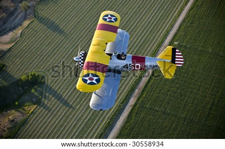 Yellow biplane over two tone fields - stock photo