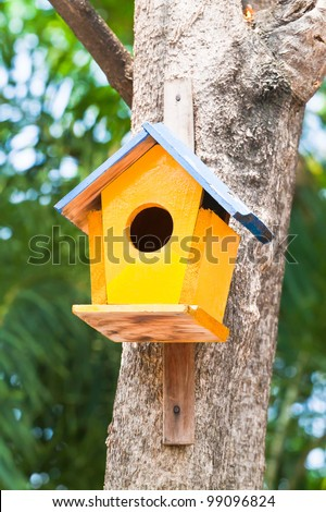 yellow birdhouse on a tree - stock photo