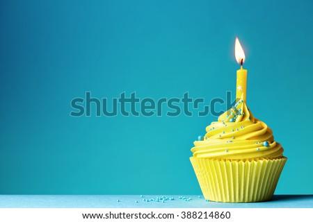 Yellow birthday cupcake on blue - stock photo