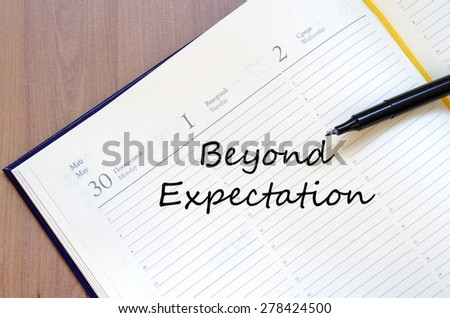 Yellow blank notepad on office wooden table Beyong expectation  concept - stock photo
