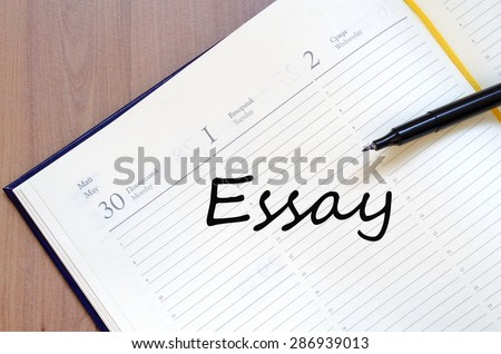 Yellow blank notepad on office wooden table Essay concept