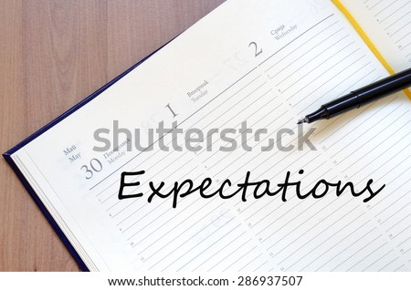 Yellow blank notepad on office wooden table Expectations concept