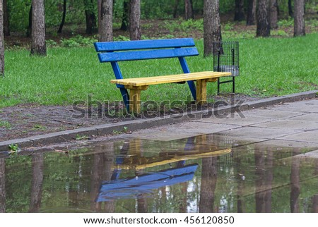Yellow-blue bench in a park in rainy weather - stock photo