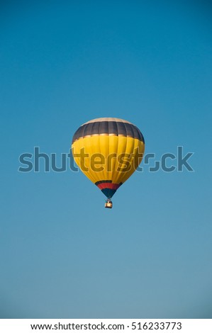 Yellow blue hot-air balloon against the blue sky. Background. Air balloon flight
