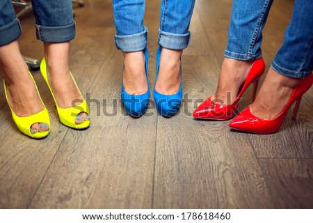 Yellow blue red shoes on female FEET - stock photo