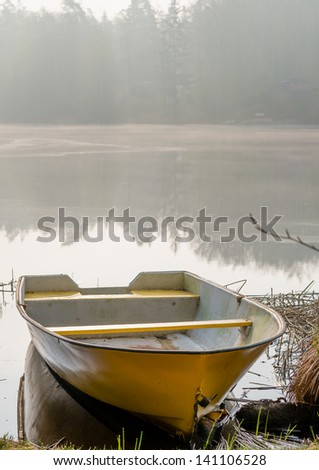 Yellow boat at the shore of lake surrounded by morning mist.