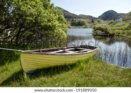 Yellow boat by lake - stock photo