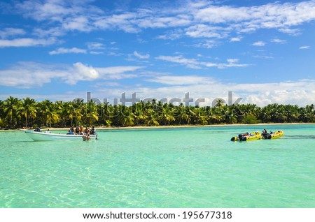 Yellow boats and people having fun on a background of azure water and the coast of an exotic island with white sandy beaches and beautiful palm trees, Caribbean Islands  - stock photo