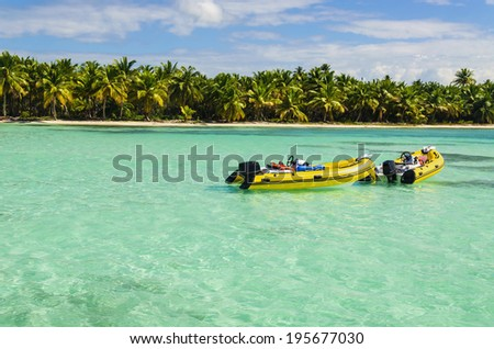 Yellow boats on a background of azure water and the coast of an exotic island with white sandy beaches and beautiful palm trees, Caribbean Islands  - stock photo