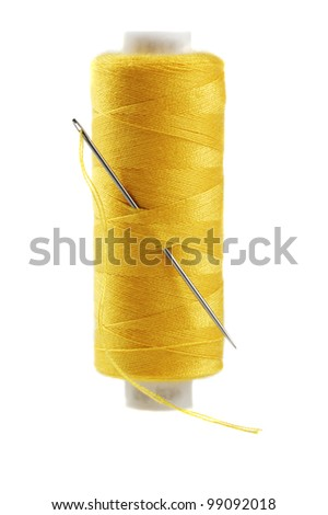 Yellow bobbin of thread with needle isolated on white - stock photo