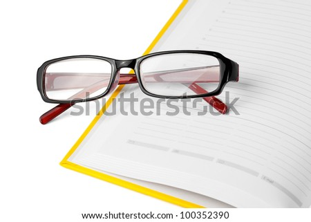 Yellow book and glasses  on a white background with blank space for your text