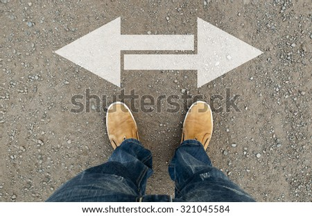 Yellow boots on the road. A man standing on the road. The road arrow