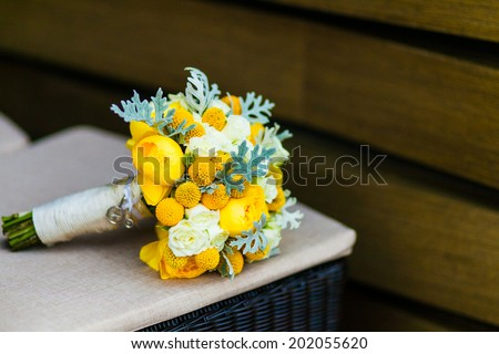 yellow bouquet of wedding flowers on wood background