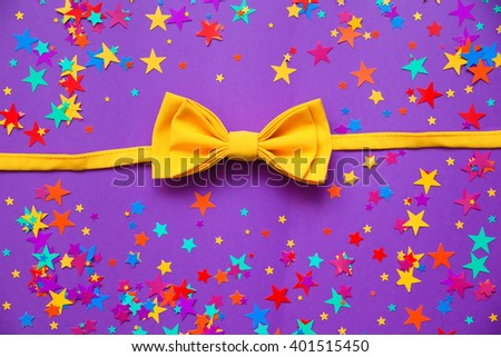 yellow bow tie and confetti on a purple background  - stock photo