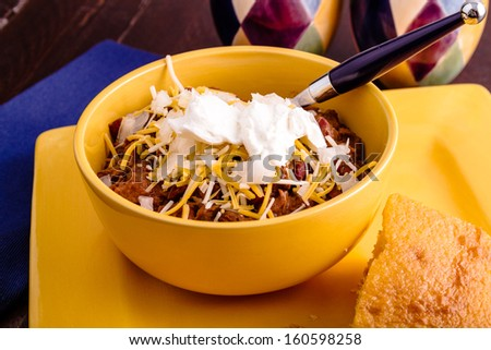 Yellow bowl filled with elk meat chili with beans, toppings and cornbread - stock photo