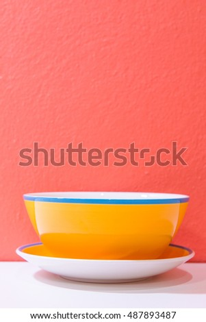 Yellow bowl with orange wall and white floor, Thailand.