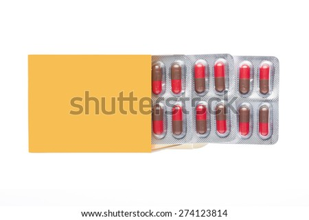 Yellow box with red pills in a blister pack on an isolated background - stock photo