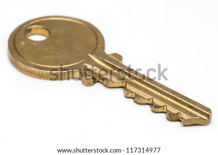 Yellow brass key on isolated white background.