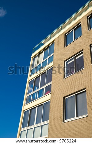yellow brick apartment building under a deep blue sky