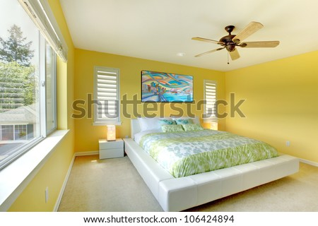 Yellow bright bedroom with green bedding and white bed. - stock photo