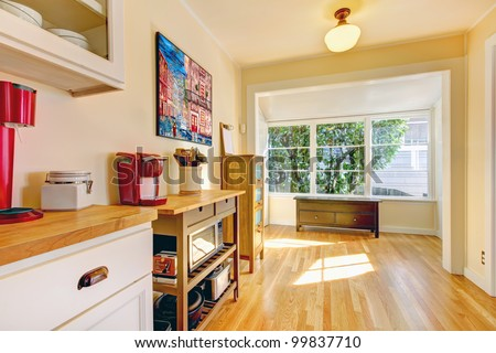 Yellow bright kitchen with large window and bench. - stock photo