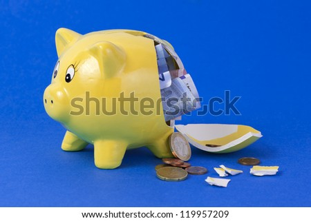 Yellow broken piggy bank containing euro bills and coins on blue background