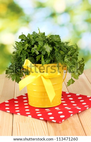 Yellow bucket with parsley and dill on wooden table on natural background - stock photo