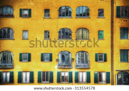 yellow building facade with green shutters in Florence, Italy - stock photo