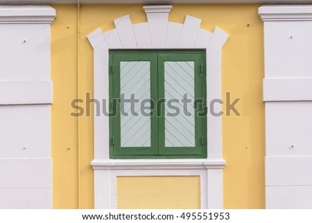 Yellow building with green windows.