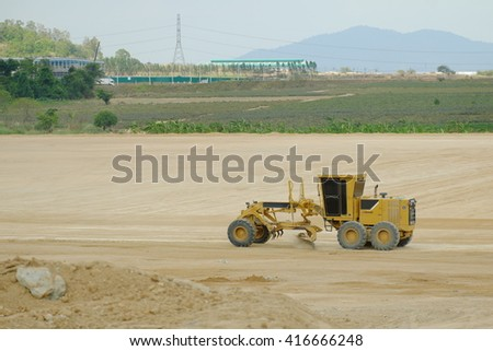 Yellow bulldozer in a field of sand - stock photo
