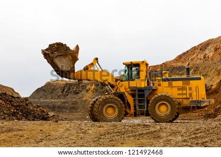Yellow bulldozer in quarry - stock photo