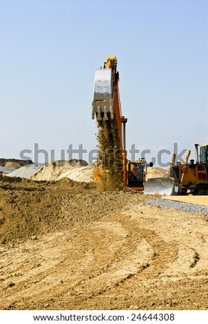 Yellow bulldozer machines digging and moving earth at construction site - stock photo